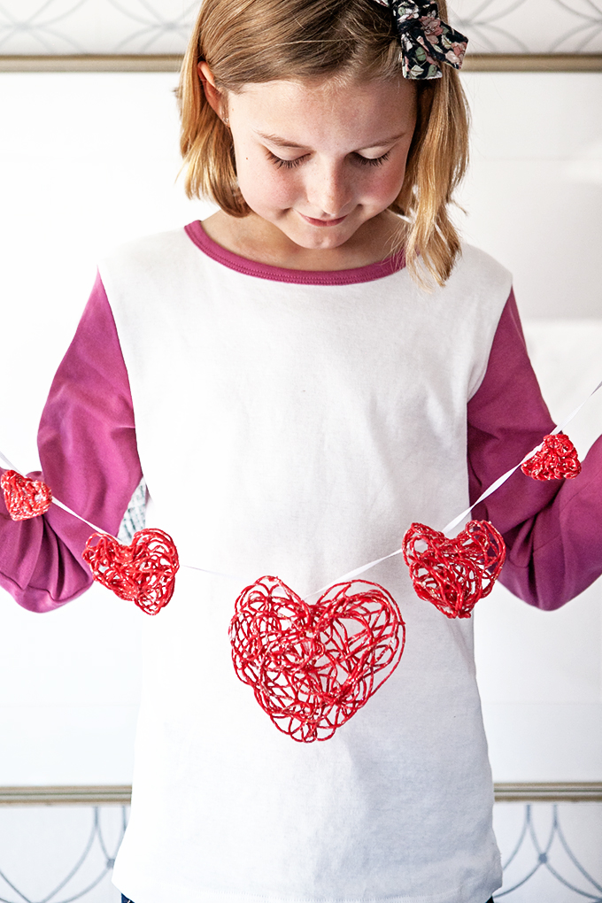Girl holding a string of valentine yarn ornaments