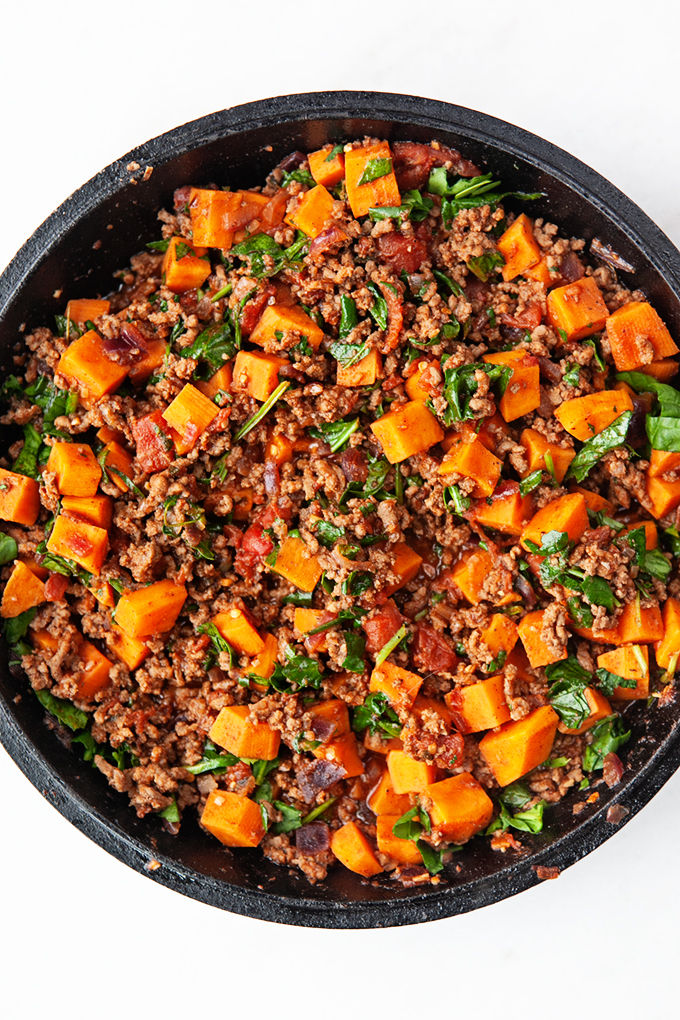 Skillet filled with ground beef, sweet potatoes, and spinach filling for stuffed peppers