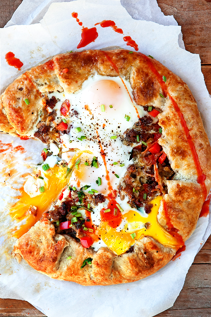 Breakfast Galette pastry topped with eggs, meat, cheese, bell peppers, greens, and a drizzle of hot sauce