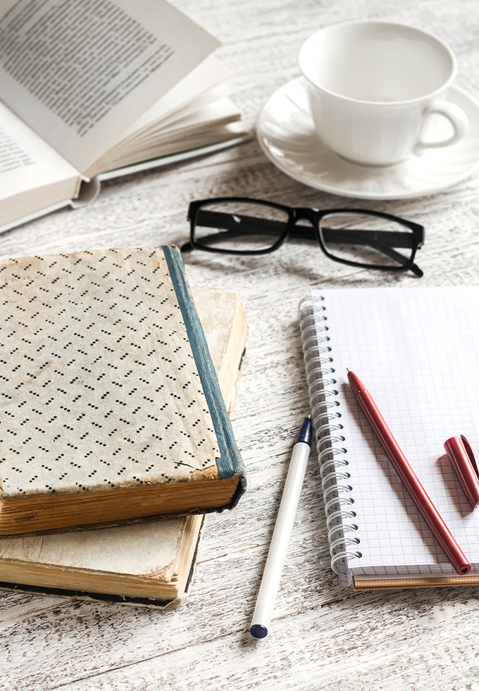 Stack of books, notebook and glasses , coffee cup on white wooden table. The concept of education and training