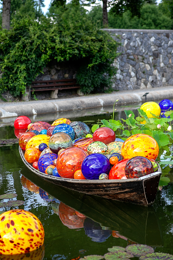 Canoe in Biltmore Pond filled with Chihuly Glass Blown Balls