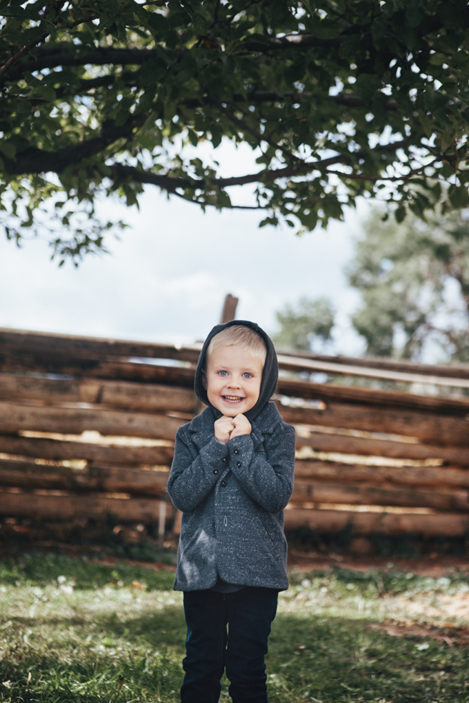 little boy in a hooded jacket under an apple tree