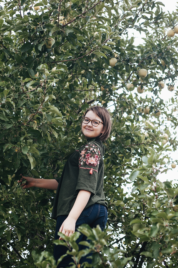 girl climbing in apple tree