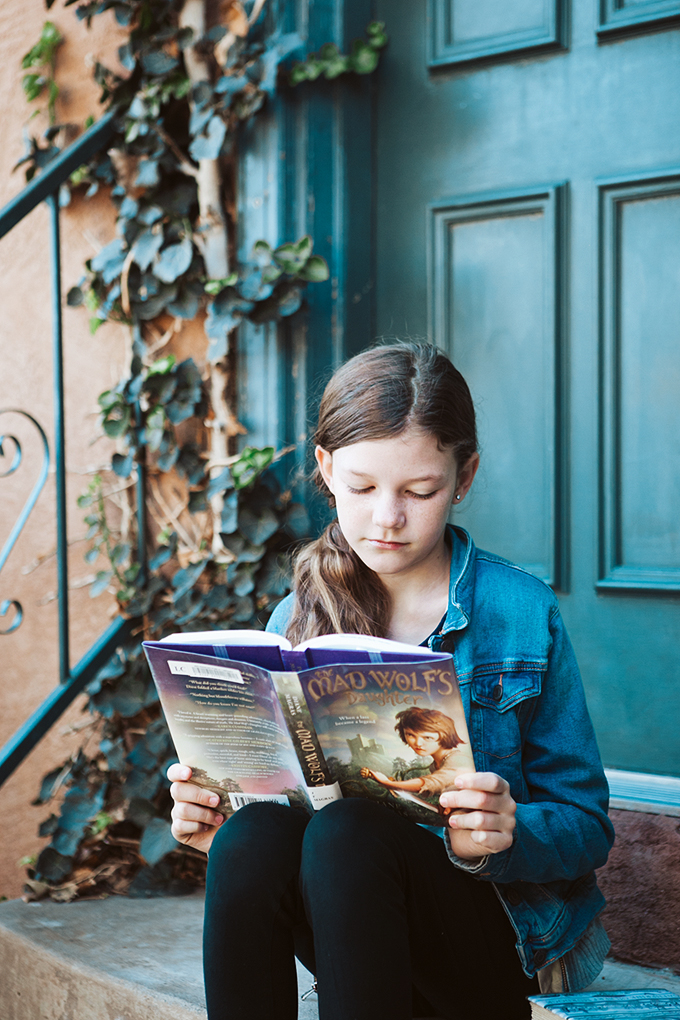 Close up of girl reading book on porch