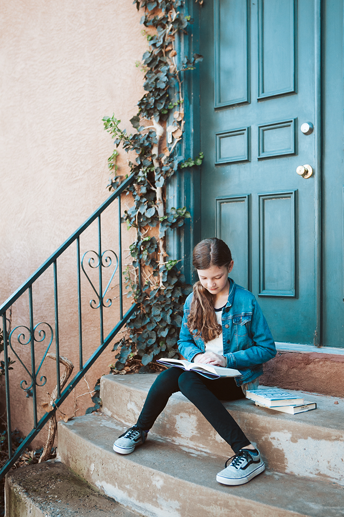 Girl sitting on porch steps reading new middle grade books