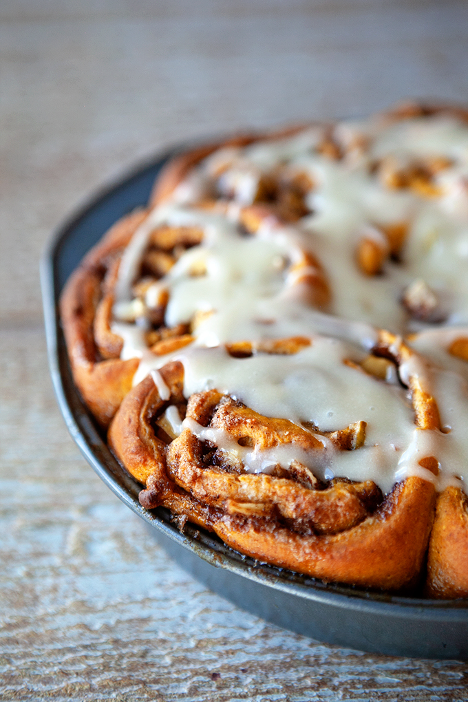 Frosted pumpkin apple cinnamon rolls in the pan