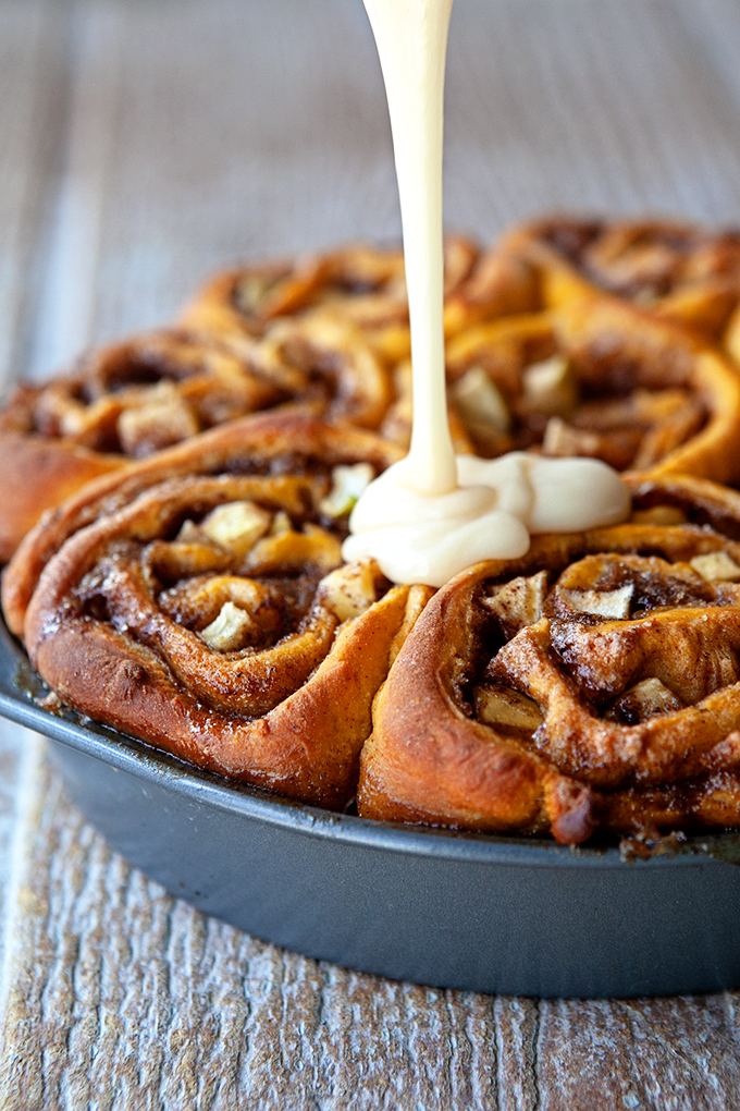 a closeup shot of frosting being poured over pumpkin apple cinnamon rolls in a round cake pan