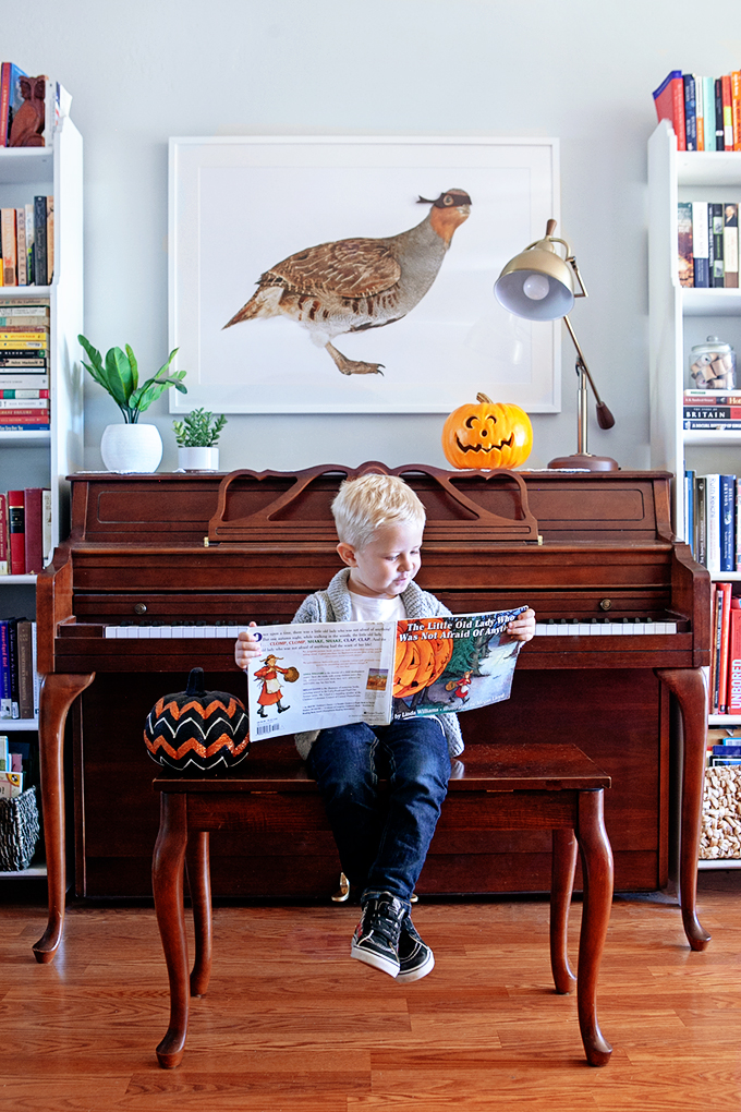 Boy reading Halloween Picture Books sitting on piano bench