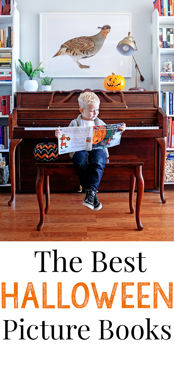 A child reading halloween picture books on a piano bench