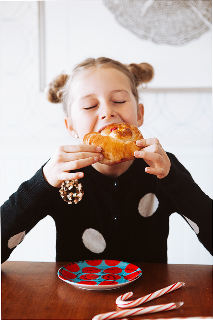Little girl taking a bite out of a large cranberry orange sweet roll