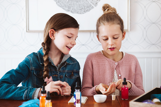 two girls using a potion making kit for kids