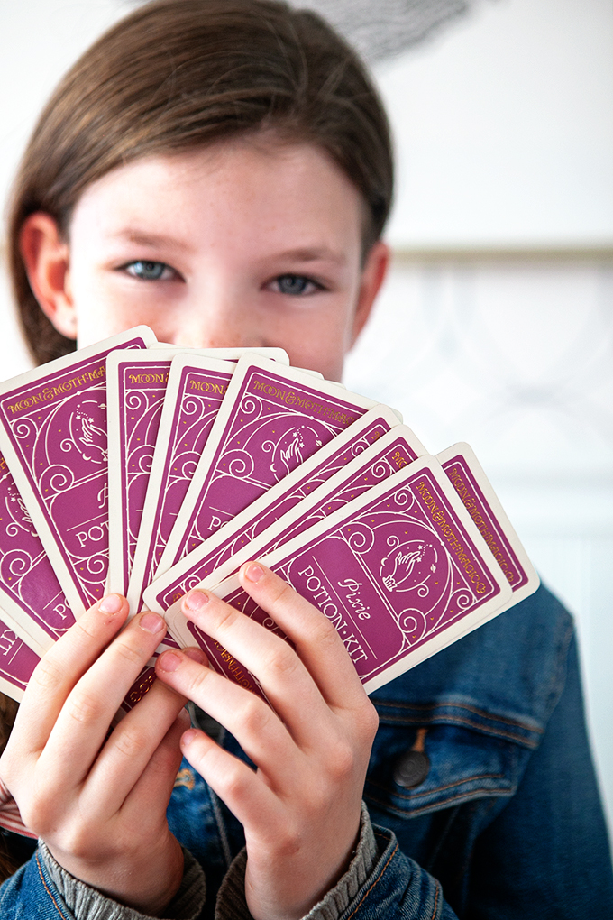 Girl holding a fan of potion cards in front of her face
