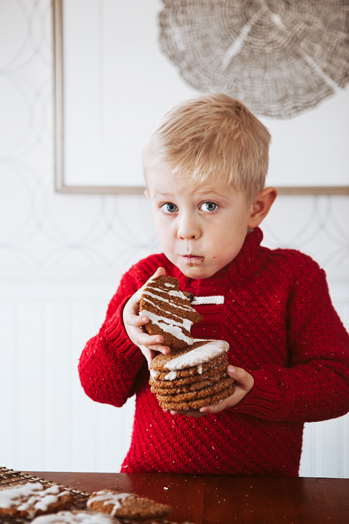Little boy holding a stack of cookies and eating one spiced ginger cookie
