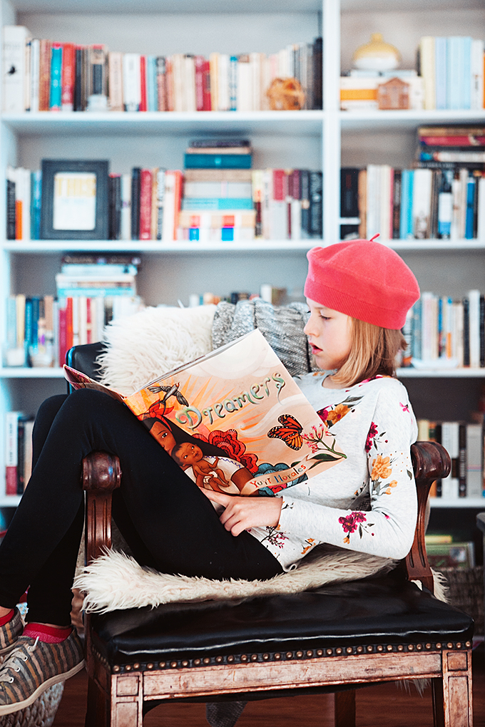 Girl reading picture book in chair in front of bookshelf for Caldecott and Newbery Predictions
