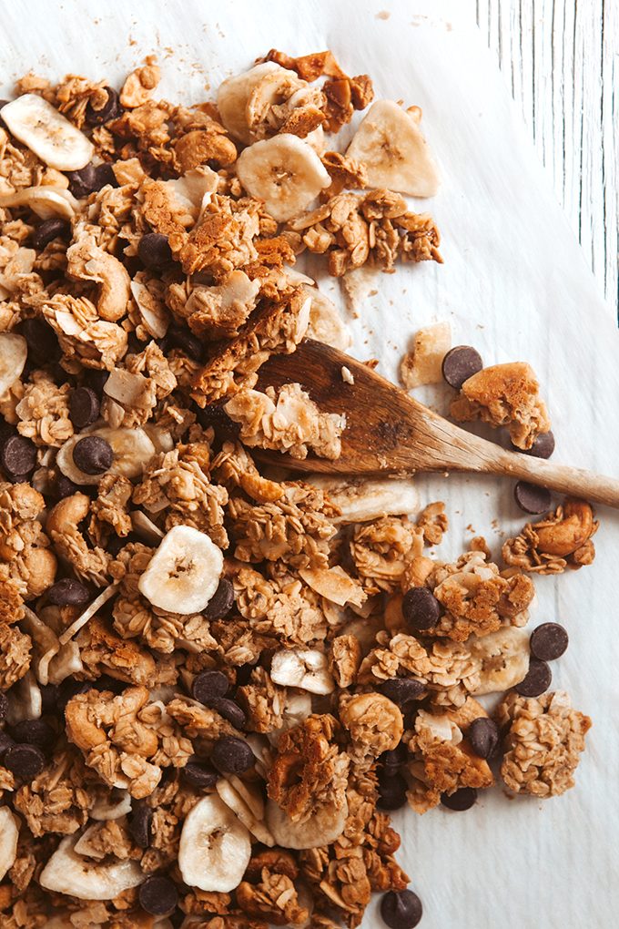 Chunky Monkey Baked Trail Mix on parchment with a wooden spoon