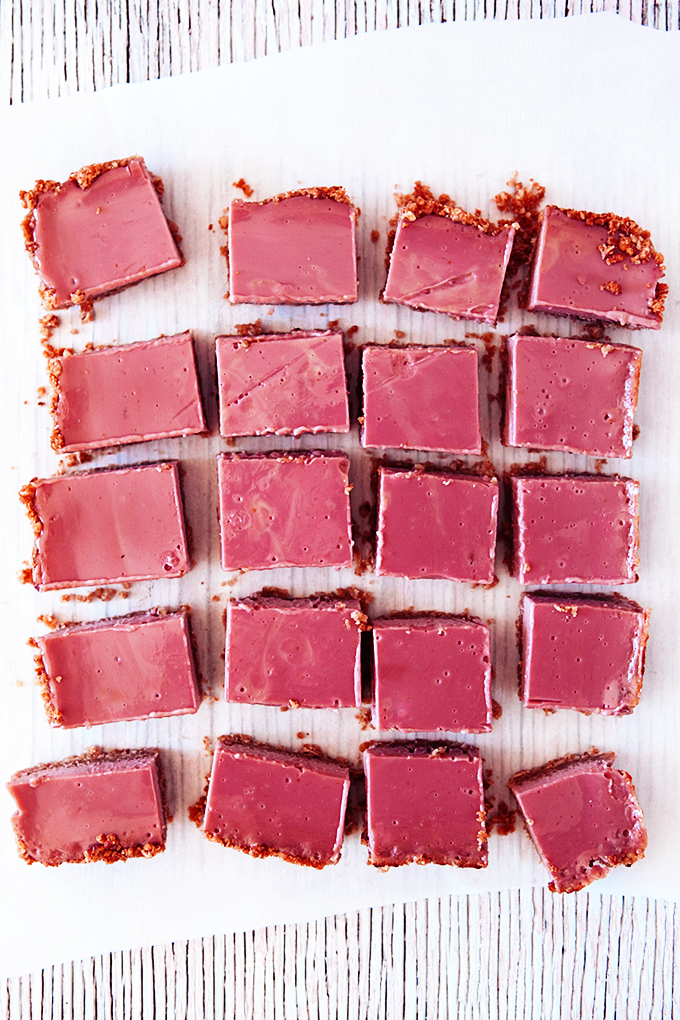 20 squares of cranberry bars on a piece of parchment paper