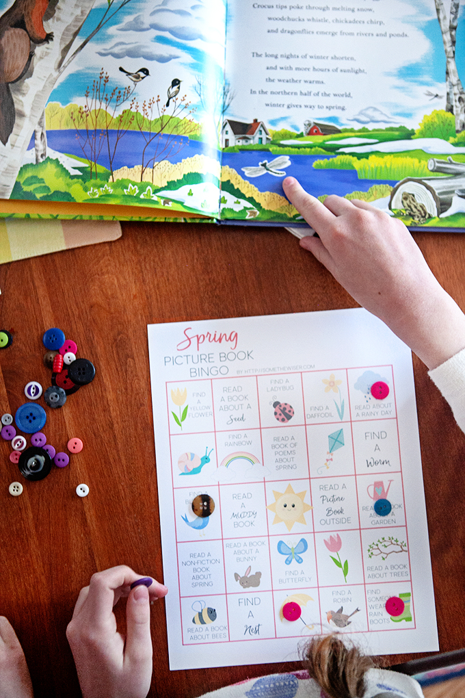 Picture Book Bingo Card with a child's hand pointing to a picture book
