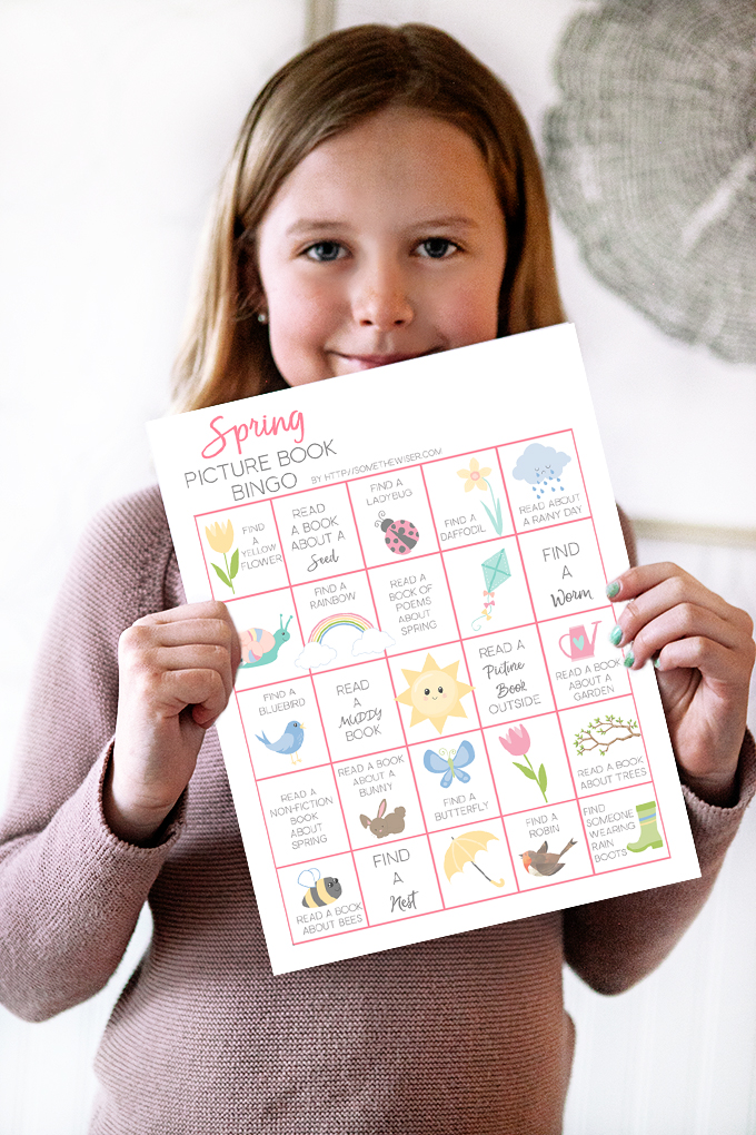 Girl holding up a picture book bingo card
