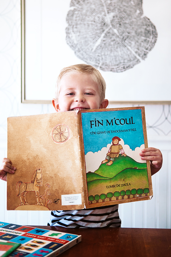 Boy holding a picture book by Tomie de Paola for a post about St. Patrick's Day Picture Books