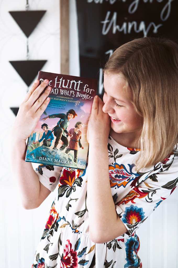 Girl holding The Hunt for the Mad Wolf's Daughter book