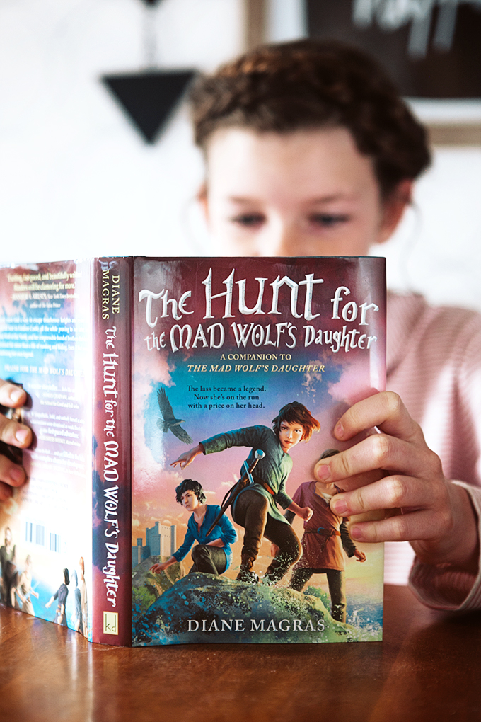A girl reading a copy of The Hunt for the Mad Wolf's Daughter