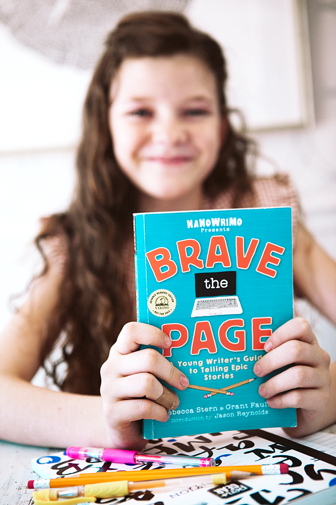 Girl holding a copy of Brave the Page with tools from her creative writing kit