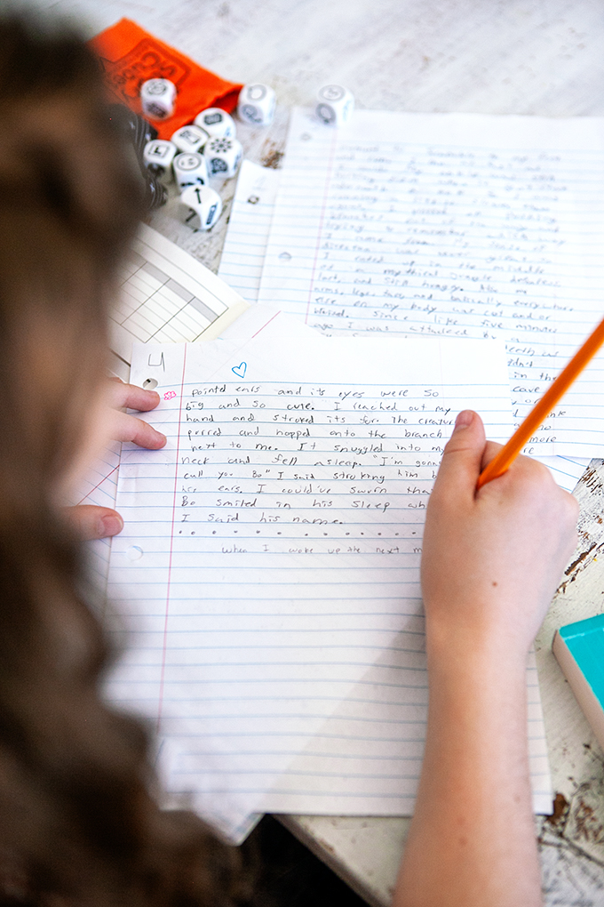 close up of a child holding a pencil and writing a story on lined paper