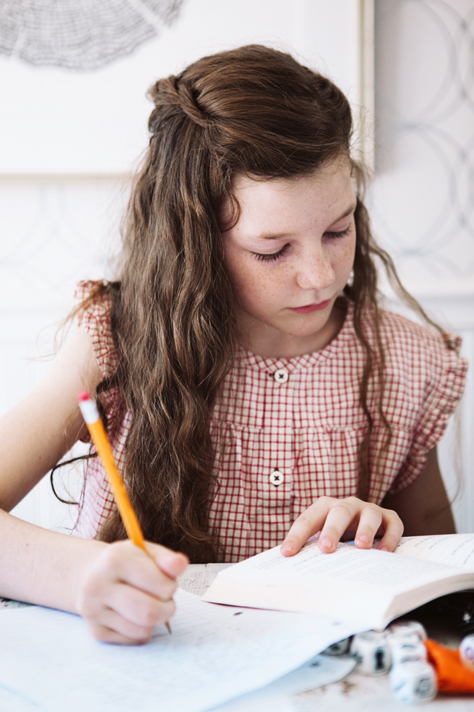 Girl writing a story with her creative writing kit