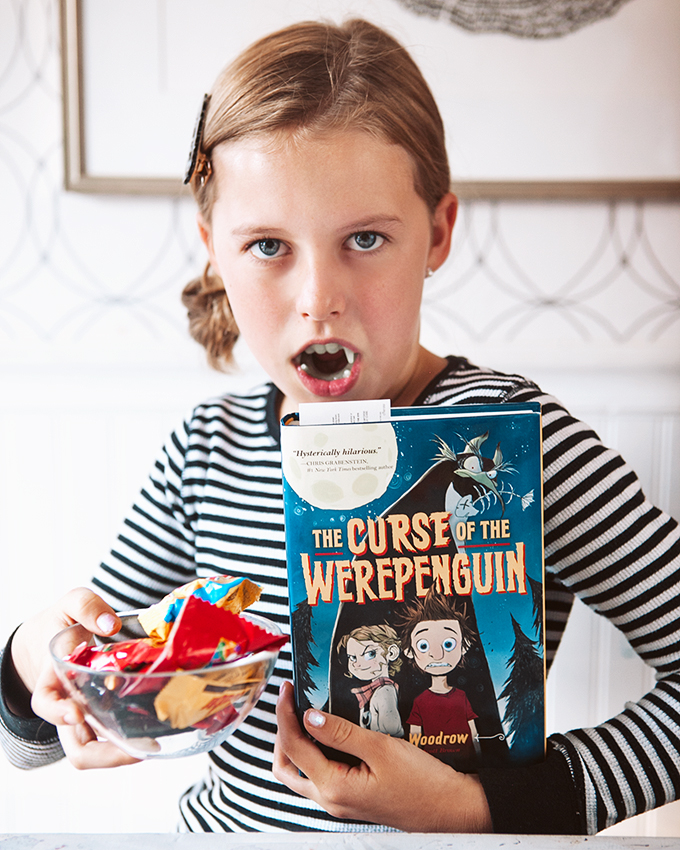 girl posing with a book and a bowl of candy for a halloween readathon for kids