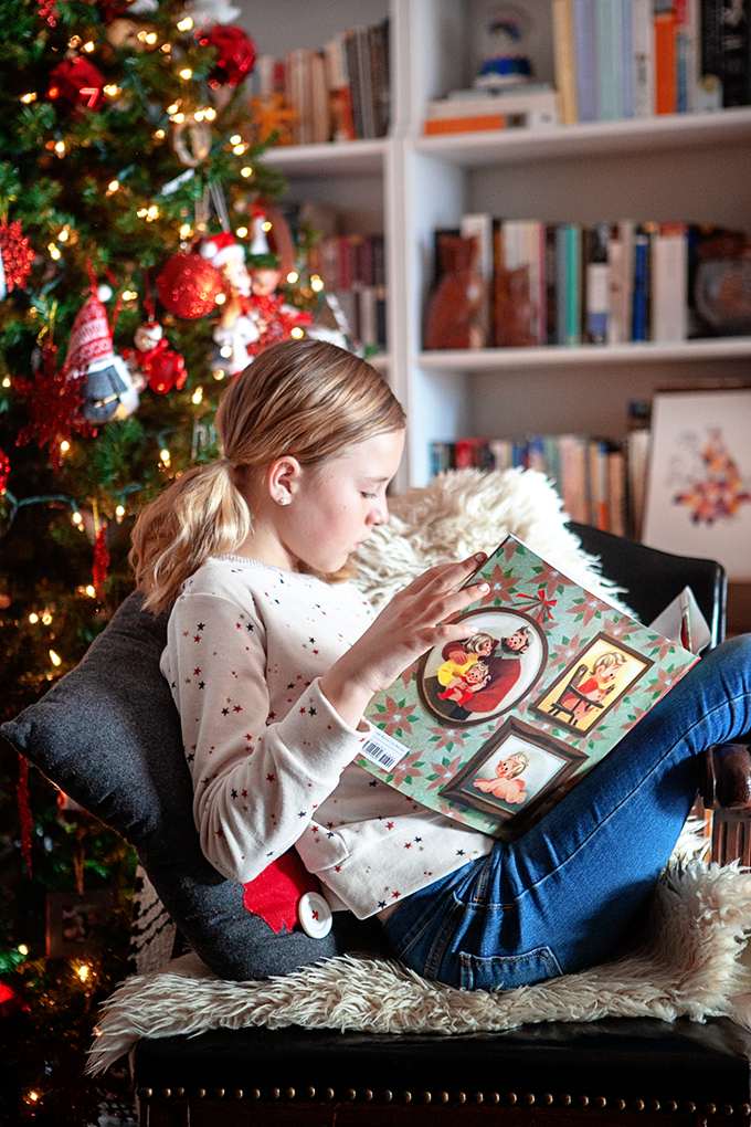 girl reading children's christmas books in front of a christmas tree