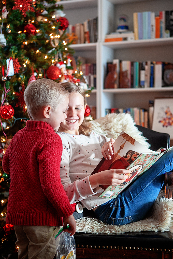 two kids reading children's christmas books in front of a christmas tree