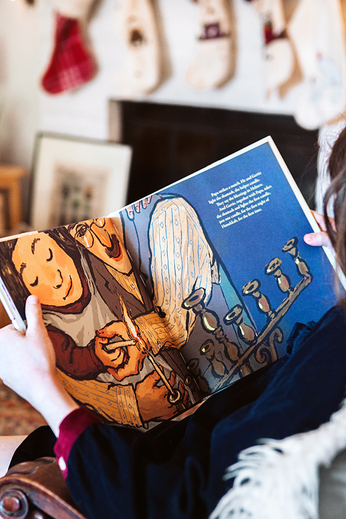 Close up of a child holding an open Hanukkah Picture Book in front of a fireplace