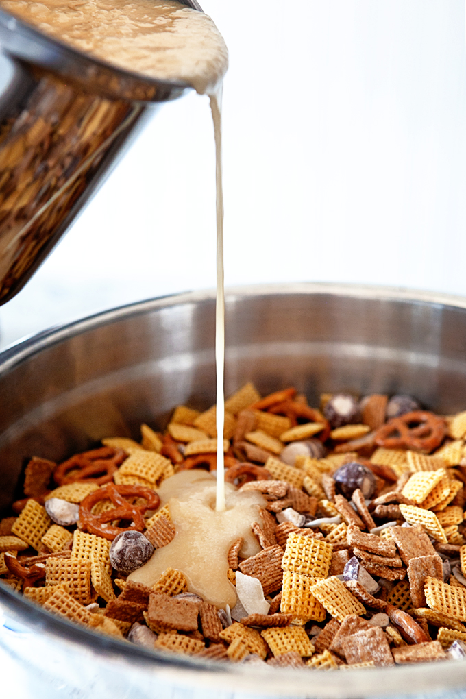 pouring the butter mixture over the malted golden graham chex mix in a bowl