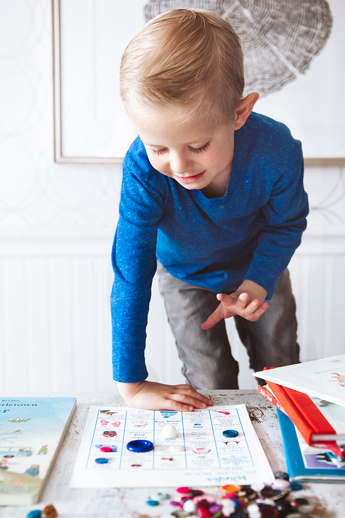 Child playing with a winter picture book bingo card