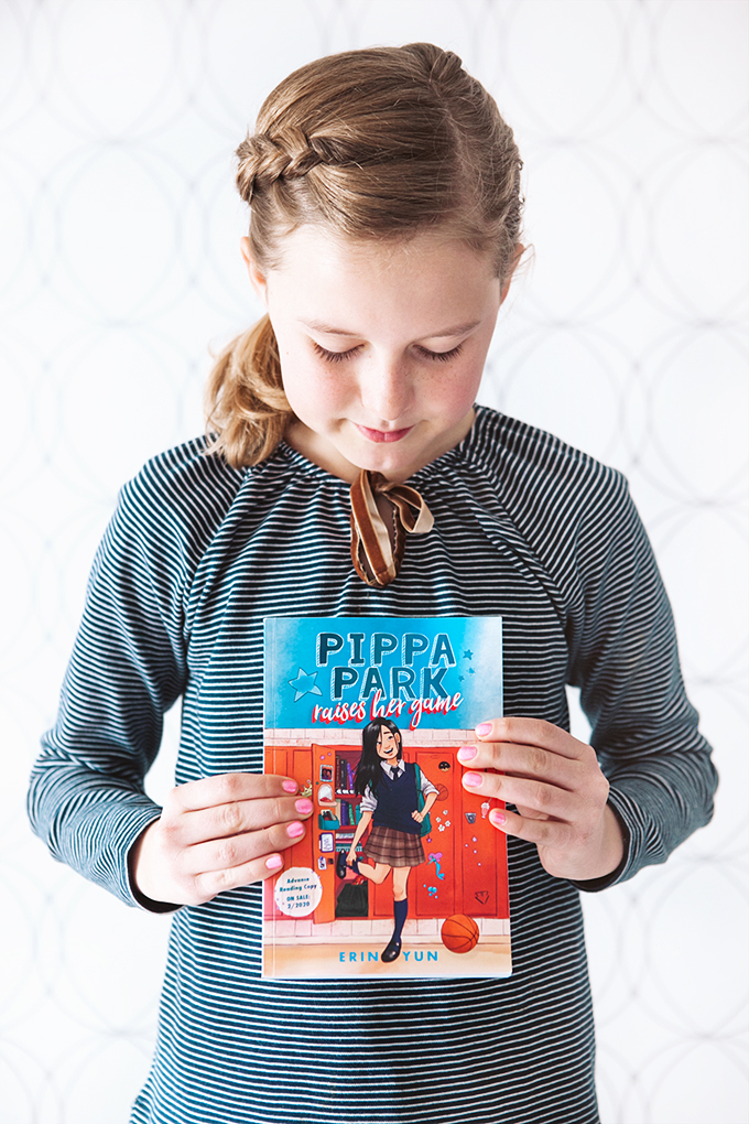 Girl holding a copy of the book Pippa Park Raises Her Game