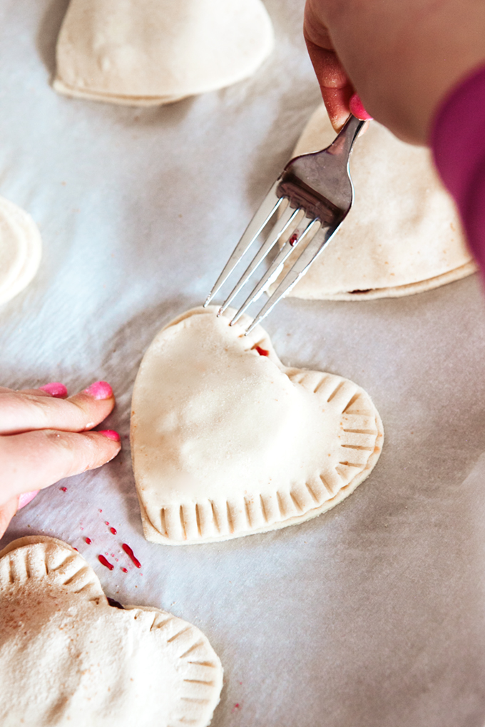 sealing the puff pastry donut hearts by pressing the edges with the tines of a fork