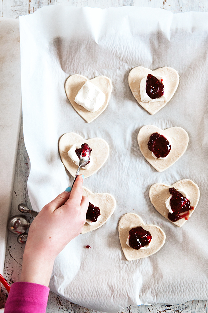 Filling stuffed puff pastry donut hearts with raspberry preserves and cream cheese