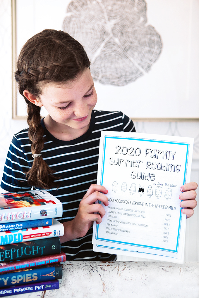 Girl with a stack of books and a family summer reading guide