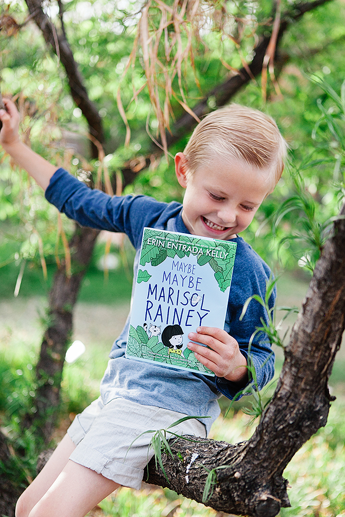 young boy holding a copy of maybe maybe marisol rainey