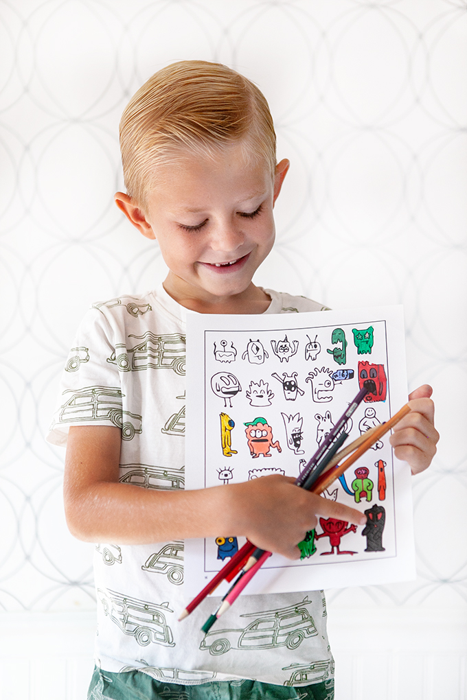 boy holding a picture of monsters from the official doodle boy coloring book
