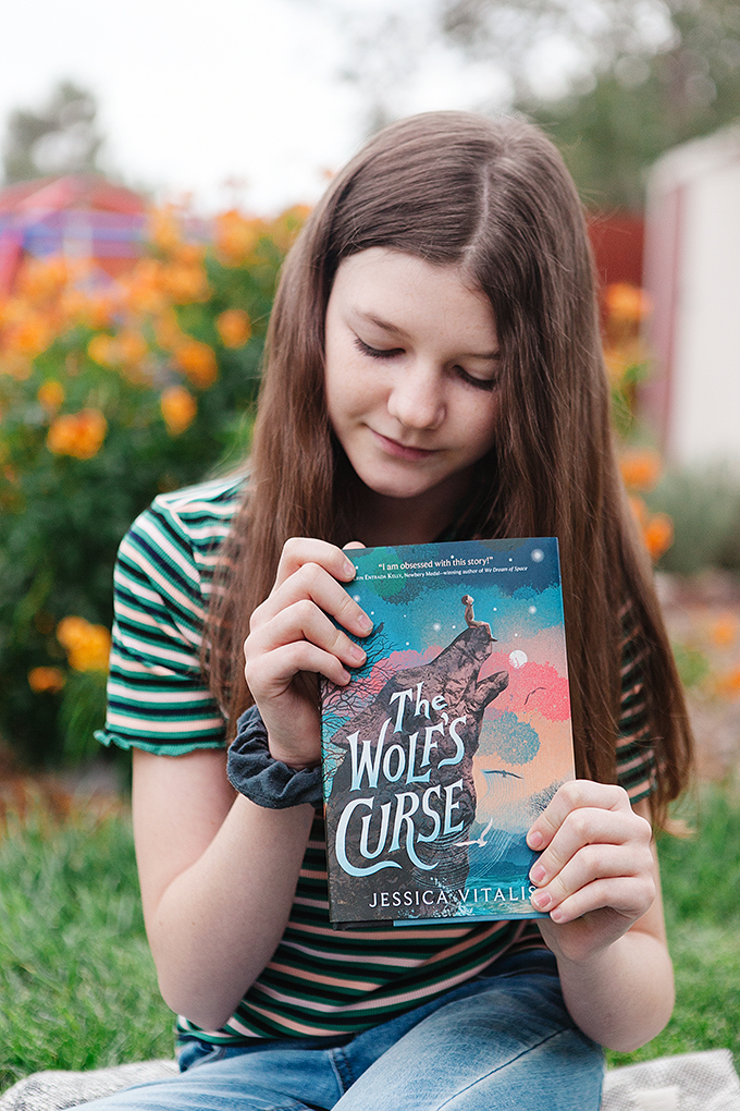 girl holding a copy of The Wolf's Curse by JEssica Vitalis